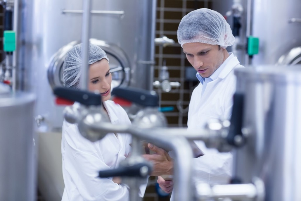 Biologist team talking and wearing hairnet in the factory
